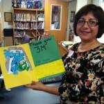 Un voluntario de 3M sostiene una tarjeta de agradecimiento de un niño