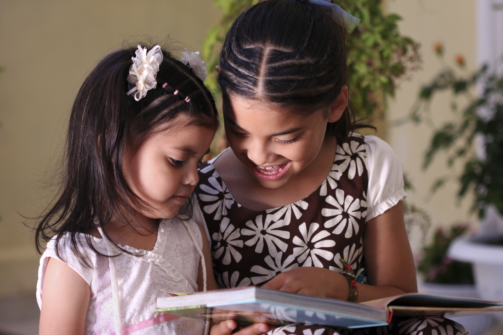 Two Hispanic Sisters Looking at Book