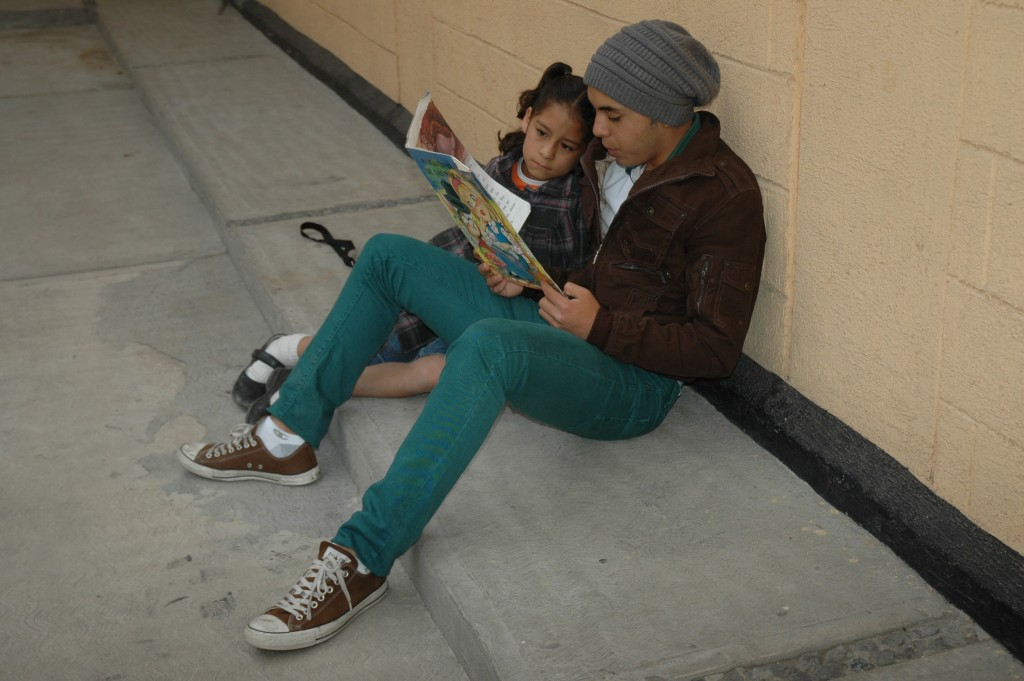 teen and child reading outdoor wall