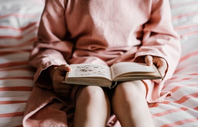 Book in girl's lap
