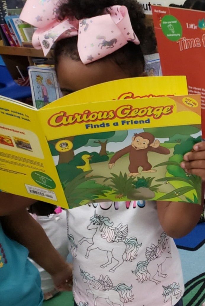Child Inc- Girl reading Curious George